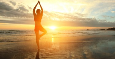 Young woman silhouette practicing yoga on the sea beach at sunset