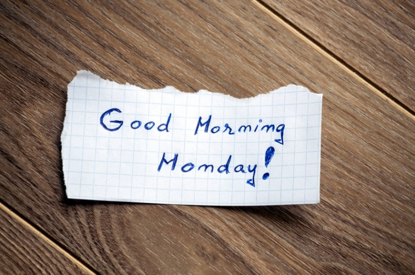 Good Morning Monday written on piece of paper, on a wood background.
