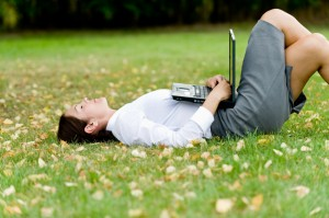 Woman-lying-on-grass-with-computer-000065031907_Small