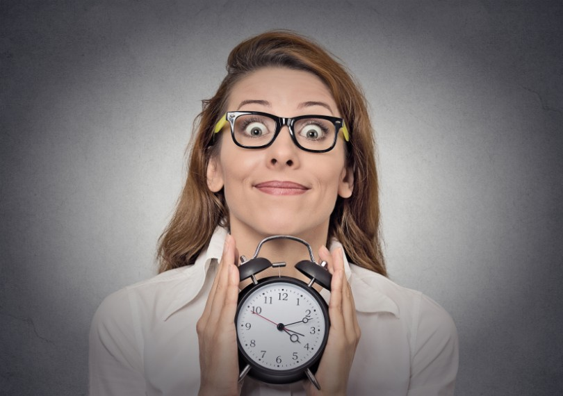 alarm clock. headshot young excited funny looking business woman holding alarm clock isolated grey wall background. Human face expressions, emotions. Time, punctuality, busy schedule concept
