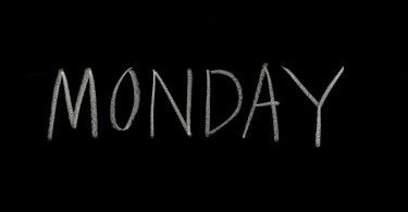 "hand writing ""monday"" on blackboard"